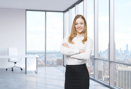 view window: Beautiful smiling employee is standing in the office with New York panoramic view. A concept of the modern workplace.