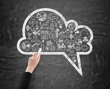 thinking cloud: A womans hand which is drawing a cloud with the range of business icons on the black chalkboard.