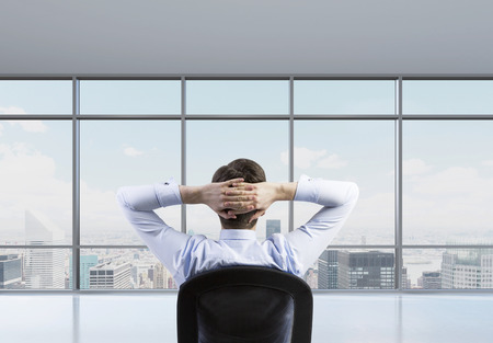 shirtsleeves: Rear view of the relaxing businessman is in a modern panoramic office. New York cityscape.