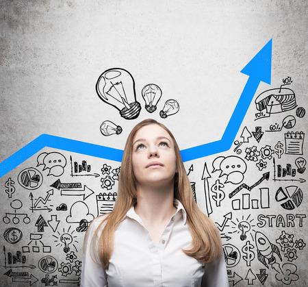 planen: Business-Dame auf der Suche nach neuen Geschäftsideen. Blau wachsenden Pfeil als ein Konzept der erfolgreichen Unternehmens. Business-Symbole werden an der Betonwand gezogen.
