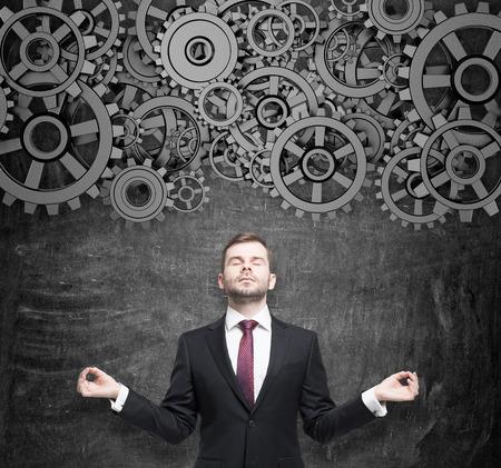 reflexionando: Empresario meditativa est� pensando en la optimizaci�n del proyecto. Engranajes como un concepto de proceso de trabajo del pensamiento. Pizarr�n negro como fondo. Foto de archivo