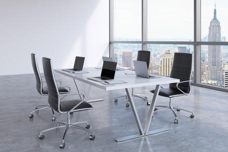 OFFICE DESK: Modern meeting room with huge windows looking at New York City. Black leather chairs and a white table with laptops. 3D rendering. Stock Photo