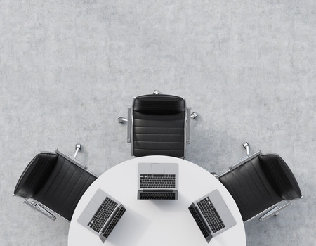 round chairs: Top view of a half of the conference room. A white round table, three black leather chairs. Three laptops are on the table. Office interior. 3D rendering. Stock Photo