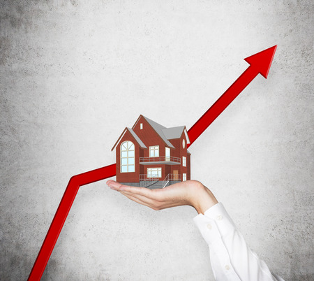 and real estate: A hand is holding a house. A huge red arrows rocketing as concept of rising real estate market. Stock Photo