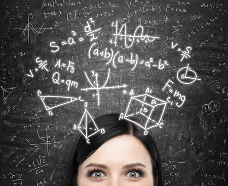 matemáticas: Un frente de la dama morena y fórmulas matemáticas se dibuja en el pizarrón negro.