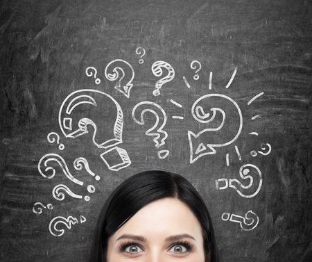 A forehead of the brunette girl who is pondering about unsolved problems. Question marks are drawn around the head. black chalkboard background.