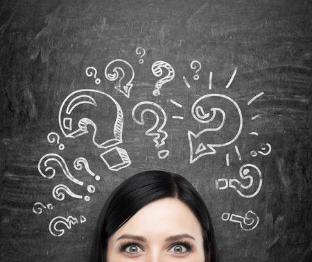 Un front de la jeune fille brune qui réfléchit sur les problèmes non résolus. Les points d'interrogation sont dessinés autour de la tête. noir tableau arrière-plan.