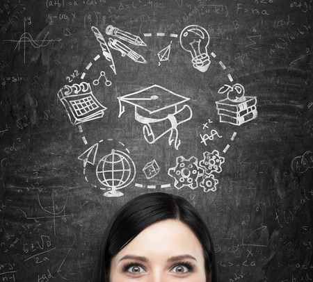 A forehead of the brunette lady who thinks about studying and graduation. Educational icons are drawn on the black chalkboard.