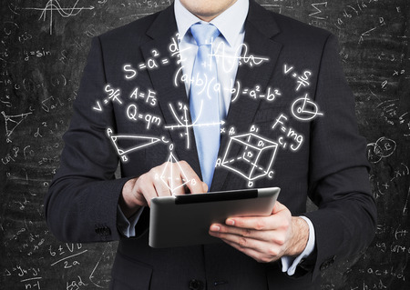 algebra calculator: Young man in formal suit is holding a tablet with math formulas projection on the air.