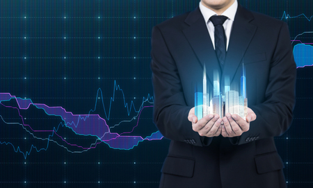 cradling: A person holds a hologram of skyscrapers as a symbol of financial success.Forex chart as a background. Stock Photo