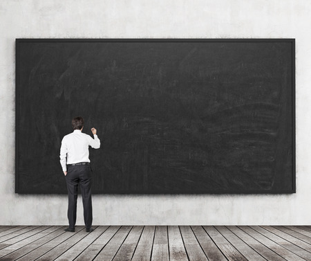 professors: Rear view of the man who is going to write something on the black chalkboard. Wooden floor and concrete wall. A concept of the beginning of new academic year. A class room.