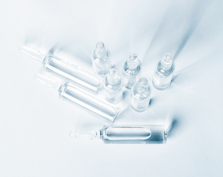 unlabelled: Top view of break-seal glass ampoule set with liquid medicine on light blue background.