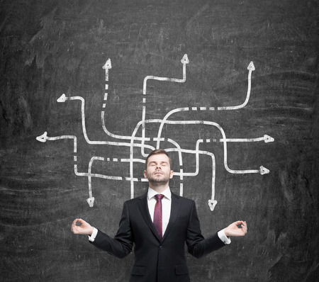 명상의 잘 생긴 사업가는 복잡한 문제의 가능한 해결책에 대해 숙고하고 있습니다. 다른 방향으로 많은 화살표가 그의 몸 주위에 그려져 있습니다. 배