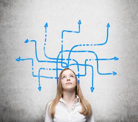 Une belle jeune femme réfléchit sur les solutions possibles du problème compliqué. Beaucoup de flèches bleues avec des directions différentes sont dessinées autour de sa tête. Mur de béton comme arrière-plan.
