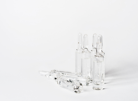 unlabelled: Break-seal glass ampoule set with liquid medicine on white background.