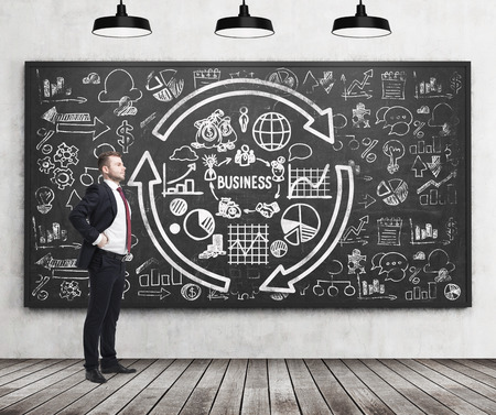 full length: Full length of a confident handsome man who presents some business plan on the black chalkboard. A concept of the professional management of start up project. Business icons are drawn on the chalkboard. Concrete wall and wooden floor. Stock Photo