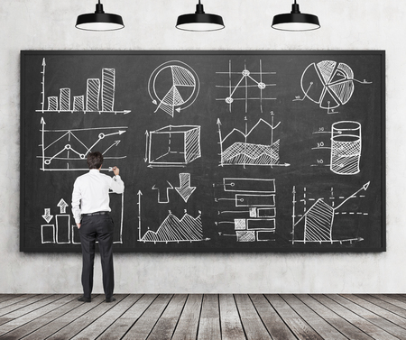 Young businessman or student of finance or management programme is drawing some charts or graphs on the black chalkboard. Rear view of the model. Wooden floor and three ceiling lights in the room. Banque d'images