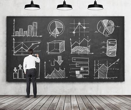 Jonge zakenman of student van de financiering of het beheer van het programma is het tekenen van een aantal grafieken of grafieken op de zwarte schoolbord. Achteraanzicht van het model. Houten vloer en drie plafond verlichting in de kamer.