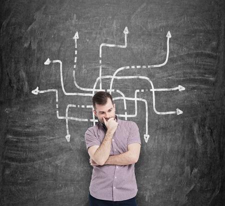 flecha direccion: Hombre joven en camisa casual sostiene la barbilla y piensa en la mejor solución del problema. Un bosquejo de las flechas en diferentes direcciones se dibuja en el pizarrón negro. Foto de archivo