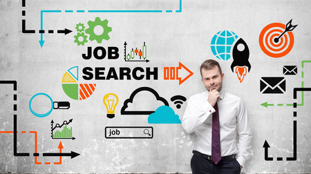 vacancies: Young man in white shirt and tie ponders on employment. Colourful icons about job vacancies are drawn on the wall. A concept of recruitment process. Concrete wall on the background. Job search.
