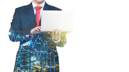 graph trend: A transparent silhouette of a man in formal suit who is looking for some data in the laptop. Panorama of evening New York city and financial charts on the background. Stock Photo