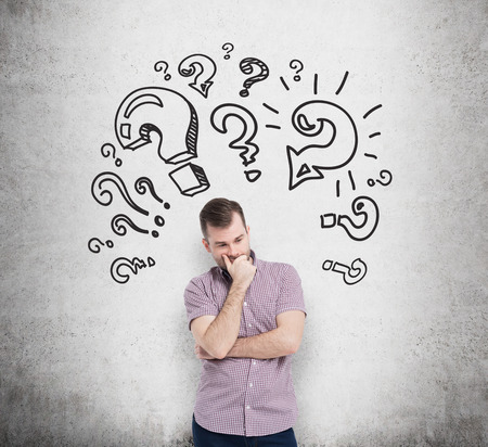 questions answers: Young man in casual shirt holds his chin and thinks about unsolved problems. Question marks are drawn around the head. Concrete wall on the background.