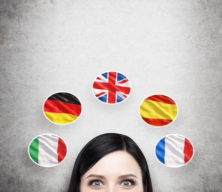 spanish language: A concept of foreign language studying process. A foreseen of the brunette girl surrounded by icons of european flags. Concrete background. Stock Photo