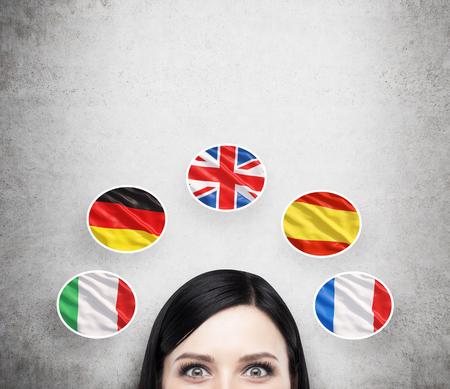 idiomas: Un concepto de proceso de estudio de lenguas extranjeras. Un previsto de la chica morena rodeado de iconos de banderas europeas. Fondo concreto. Foto de archivo