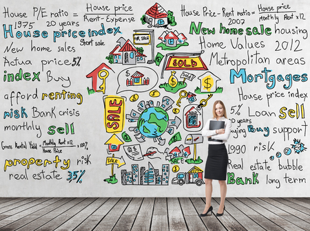 Full length beautiful woman in formal clothes holds a black folder. Colourful home sales icons are drawn on the concrete wall. Risk analysis of the mortgage loan. Wooden floor.