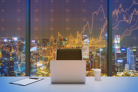 financial services: A workplace in a modern panoramic office with New York evening view and financial chart over the window. Laptop, writing pad and a cap of coffee are on the table. Office interior. 3D rendering. Stock Photo