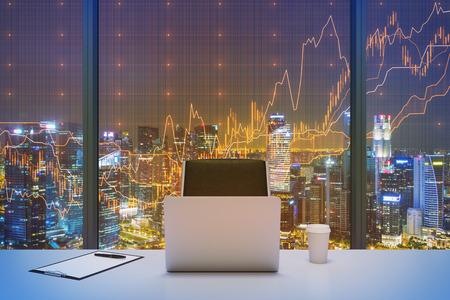 Un lieu de travail dans un bureau panoramique moderne avec New York, vue le soir et le tableau financier sur la fenêtre. Ordinateur portable, bloc-notes et un chapeau de café sont sur la table. intérieur Office. rendu 3D.