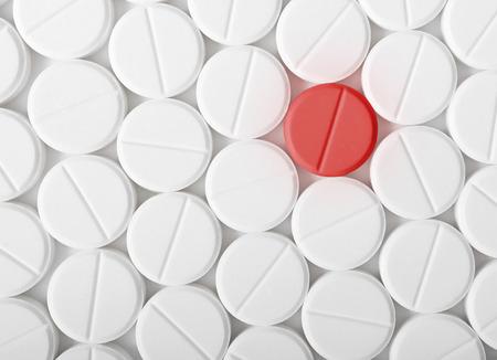흰색 표면에 흰색 약 알 약의 힙의 상위 뷰입니다. 하나의 빨간색 의학 태블릿은 백신의 개념과 같습니다.