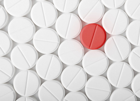pill: Top view of the heap of white medicine pills on white surface. One red medicine tablet is as a concept of a vaccine. Stock Photo