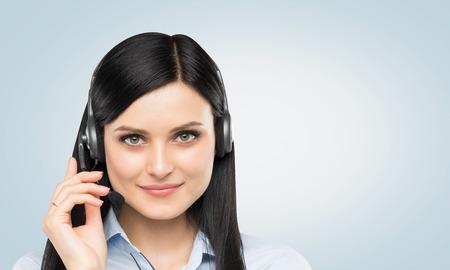 Vista frontal de la operadora de telefonía de apoyo morena sonriente con auriculares. Fondo azul claro.