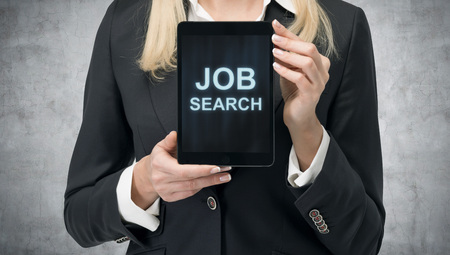 programmes: Blonde woman in formal suit presents a tablet with the words Job Search on the screen. A concept of recruitment process. Internship and graduate programmes. Concrete background.
