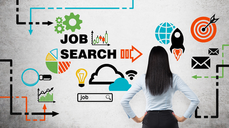 internship: Rear view of the brunette woman who is looking at the wall with colourful icons about job vacancies. A concept of recruitment process. Internship and graduate programmes. Concrete wall. Stock Photo