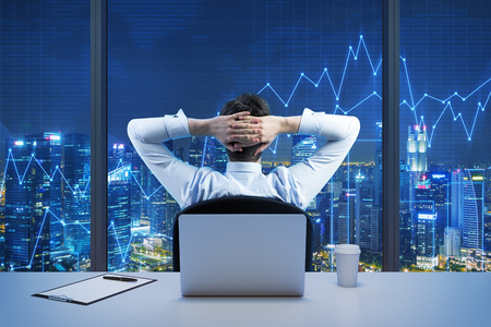 trade: Rear view of sitting businessman who is looking at the city from the modern panoramic office. New York evening view. Crossed hands on the head. Financial charts are drawn over the panoramic windows. Stock Photo