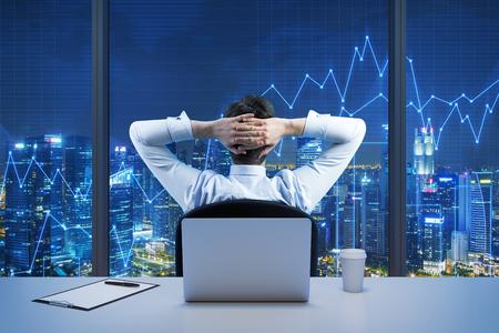 Vue arrière de la séance d'affaires qui regarde la ville du bureau panoramique moderne. New York Vue du soir. Traversé mains sur la tête. tableaux financiers sont établis sur les fenêtres panoramiques.