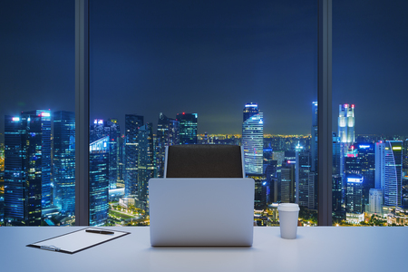 A workplace in a modern panoramic office with New York evening view. A white table, black leather chair. Laptop, writing pad and a cap of coffee are on the table. Office interior. 3D rendering. Foto de archivo