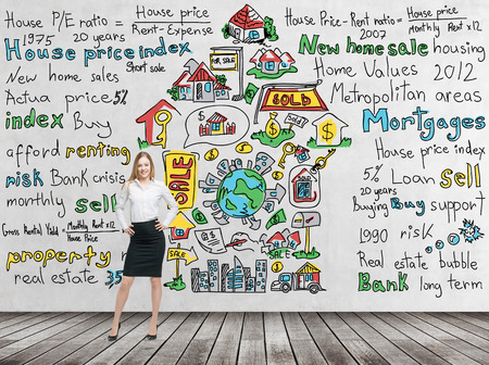 estate: Full length beautiful woman in formal clothes with hands on the waist. Colourful  home sales  icons are drawn on the concrete wall. Risk analysis of the mortgage loan. Wooden floor.