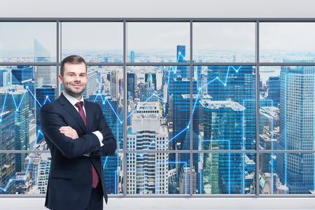panoramic windows: Smiling handsome businessman with cross hands is standing in the modern panoramic office. Financial charts are drawn over panoramic windows. New York cityscape. Manhattan. Stock Photo