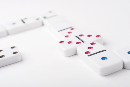 chain reaction: White domino pieces with colorful points. White background. Stock Photo