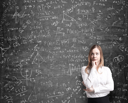 formulae: Beautiful lady in formal clothes thinking about possible solutions of the quantitative problems. Math formulas are drawn on the black chalkboard.