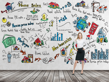 money risk: Full length beautiful woman in formal clothes with hands on the waist. Colourful home sales icons are drawn on the concrete wall. Risk analysis of the mortgage loan. Wooden floor. Stock Photo