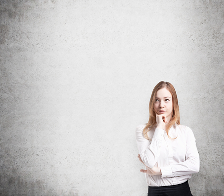 lady: Beautiful lady in formal clothes pondering on future business or career perspectives. Concrete wall on thee background.
