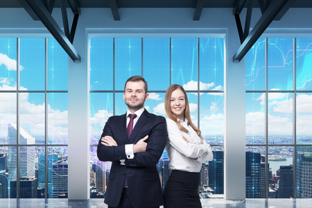 advisers: Couple of young managers are standing in the modern panoramic office. New York view. Financial charts are drawn over the panoramic windows.
