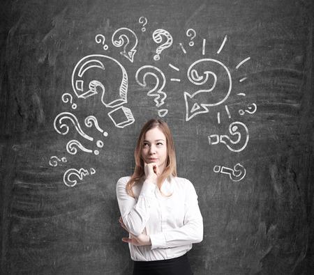 punto interrogativo: Bella giovane donna in abiti formali tiene il mento e pensa a problemi irrisolti. I punti interrogativi sono disegnati intorno alla testa. Lavagna nera su sfondo.