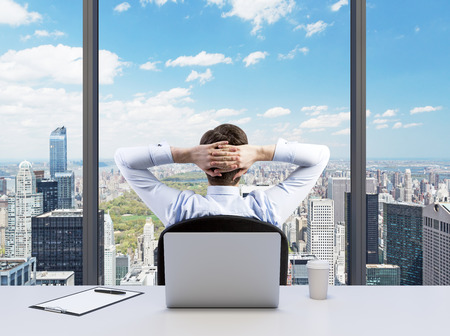 hands behind head: Rear view of the relaxing businessman with crossed hands behind his head, who is looking at the Cntral park. Modern Panoramic office or work place with New York city view.