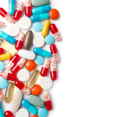 A top view of a heap of colourful medicine pills and capsules on white surface. Copy space for the ads.