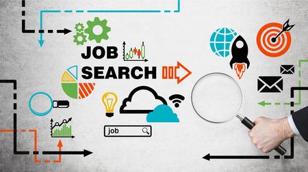 competencias laborales: Una mano sostiene una lupa. Iconos de búsqueda de empleo se dibujan en el muro de hormigón. Buscando las nuevas vacantes disponibles. Foto de archivo
